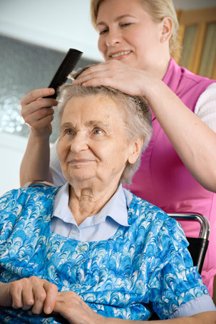 Home carer combing elderly lady's hair