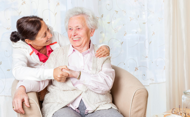 Live-in home carer with elderly lady in sitting chair